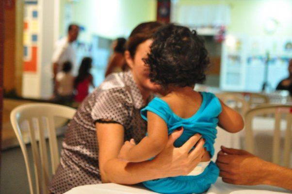 mulher abraçando criança em adoção